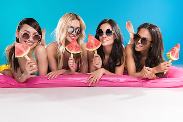 multiethnic girls in sunglasses holding watermelon pieces while lying on swimming mattress