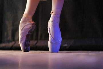 The ballerina performs the dance movement at the rehearsal in the theater