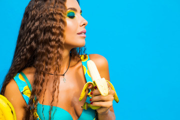 Close-up portrait of a beautiful young girl in profile, eating bananas, perfect face, bright make-up, long curly hair, fashion accessories, funny image, look, on a turquoise background, life style