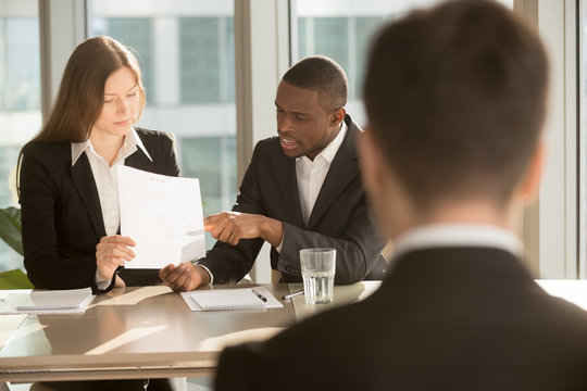 Multiracial employers or recruiters making hiring decision, discussing resume while job applicant waiting for result, employee selection team considering candidate cv before after personal interview