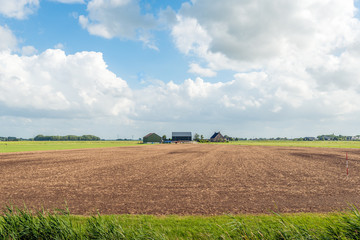 Cultivated soil in front of a modern Dutch farmhouse with barns