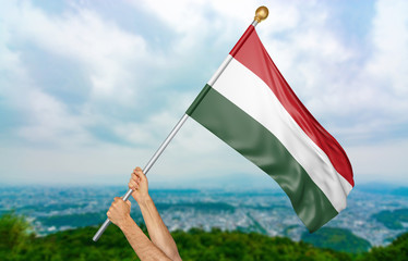 Young man's hands proudly waving the Hungary national flag in the sky, part 3D rendering
