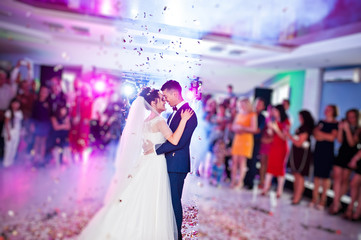 Fototapeta Touching and emotional first dance of the couple on their wedding with confetti and colorful lights on the background. obraz