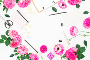 Minimalistic stylish frame workspace with clipboard, notebook, pink flowers and accessories on white background. Flat lay, top view.