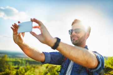 Man hiker taking photo with smartphone during trekking trip