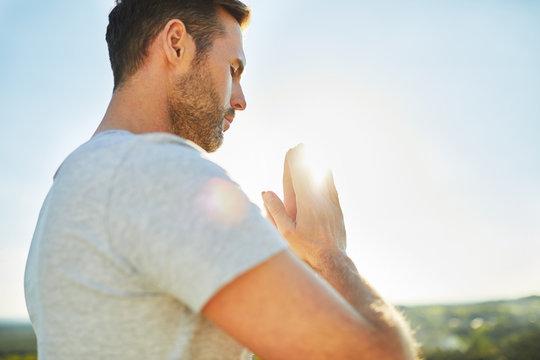 Adult man meditating, praying outdoors. Joga exercise outdoors