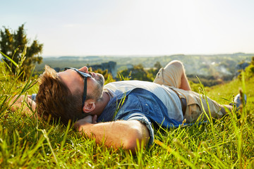 Man lying on grass enjoying peaceful sunny day Fotomurais