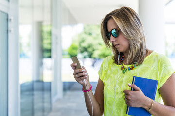 Young confident woman working outdoors and texting with her smart phone while holding an agenda in the other hands,
