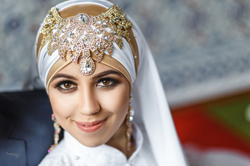 Asian Muslim bride in white decorated with golden arabic jewelry hijab and scarf, concept of oriental wedding