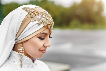 Charming muslim arabic bride in nikah wedding dress and hijab headscarf, close-up on jewelry and earrings