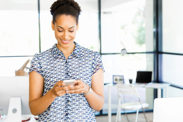 Portrait of smiling afro-american office worker with her mobile phone in offfice