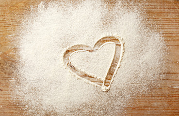 Heart drawn on flour on wooden background