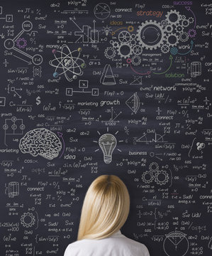 Business woman thinking and looking blackboard