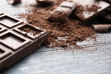 Fototapete - Dark chocolate pieces on wooden table