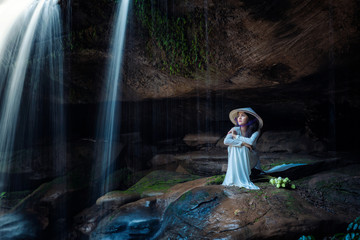 Vietnamese girl sitting lonely on a rock at a waterfall.