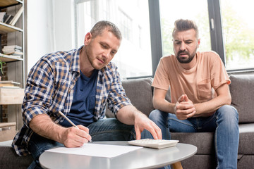Serious homosexual couple sitting together and counting family budget at home
