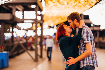 Happy couple embracing and kissing in the evening on a light garlands