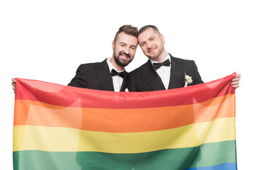 smiling homosexual wedding couple holding lgbt flag isolated on white