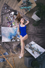 Young female artist painting abstract picture in studio, beautiful sexy woman portrait