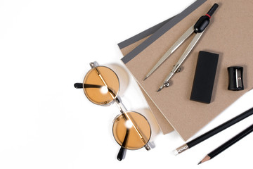 Modern white office desk table with pencil, notebook, divider scriber and glasses or office supplies with copy space for text. Top view flat lay of business desk art.