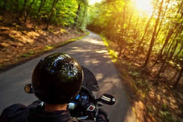 Close-up of motorbiker riding on empty road in forest with sunset light, concept of speed and touring in nature.