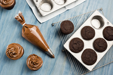 Decorating Chocolate Cupcakes with Chocolate Buttercream Frosting in Pastry Bag