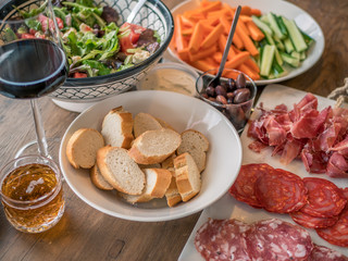 Wine appetizer set. Glass of red wine, baguette, olives, smoked meat, salad and salami on a rustic wooden table.