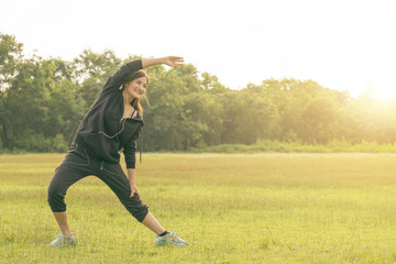 Portrait of fit and sporty young woman doing stretching in jungle trail in early morning..