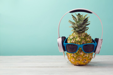 Photo sur Plexiglas Magasin de musique Pineapple with headphones and sunglasses on wooden table over mint background. Tropical summer vacation and beach party concept.