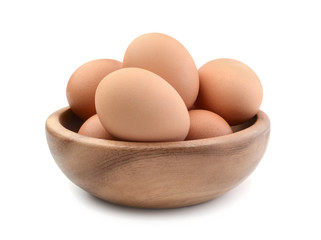 Chicken eggs in a wooden bowl isolated