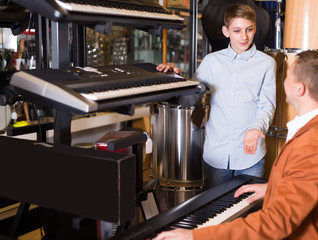 Boy and father deciding on synthesizer