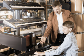 Ordinary boy and father deciding on synthesizer