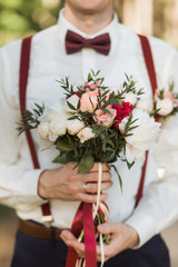 Closeup of young handsome stylish groom holding perfect bridal bouquet of fresh flowers in hands. Man wearing white shirt, brown suspenders, bowtie. Beautiful set of matching floral bunch and corsage