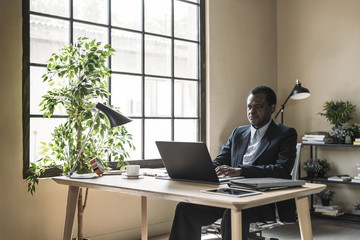 Middle-aged African businessman sitting at office and typing on his laptop.