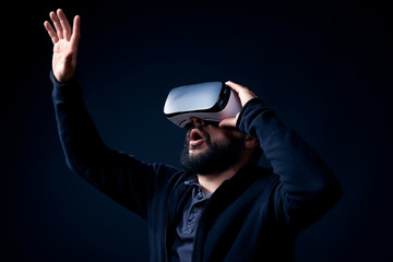 Young hipster bearded man wearing virtual reality goggles. Black background studio VR concept.