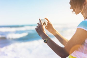 Hipster girl photograph on smart phone gadget in sand coastline, mock up of blank screen. Traveler hold and using in female hand mobile on background seascape horizon blue sun ocean, lifestyle