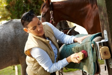 Young woman cleaning saddlery
