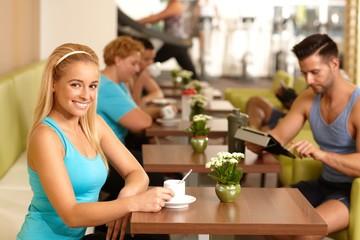 Pretty blond having coffee-break in gym