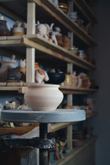 Clay pot in the foreground and shelves with pottery - on the second