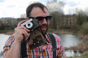 beard man with retro camera in the park