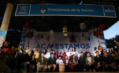 """Young people pose for pictures after receiving musical instruments during an event as part of the """"We're Here"""" Argentine government program in San Miguel"""