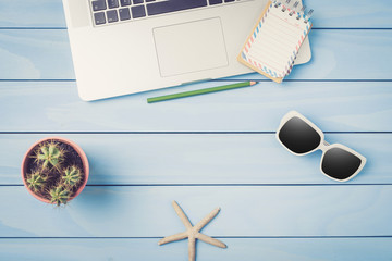 Laptop, sunglasses and cactus on blue wooden table