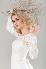 fashionable dress, beautiful blonde model, bride hairstyle and makeup concept - pretty young woman in white wedding gown standing indoors on light background, female posing with bouquet in hands