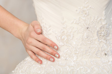 fashionable gown, beautiful model, bride and accessories concept - white wedding dress with embroidery flowers, embellished with rhinestones and pearls, hand of slender woman on the waist