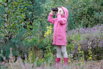 Little girl with binoculars birdwatching in summer forest