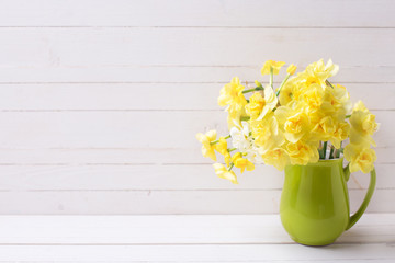 Bright yellow spring daffodils or narcissus flowers in pitcher on light wooden background.