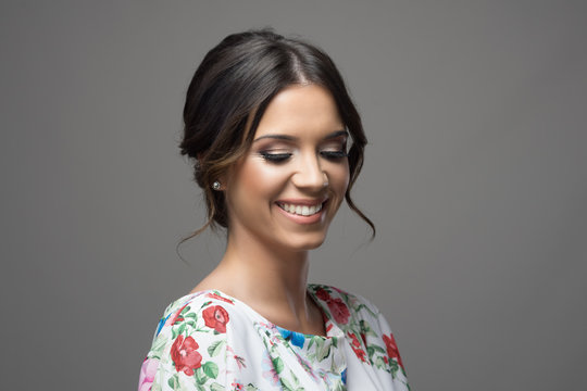 Gorgeous young shy woman with smokey eyes make up and perfect teeth smiling and looking down over gray studio background.