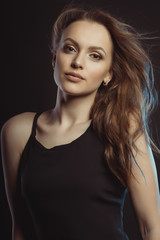 Closeup photo of beautiful young model with curly hair in motion