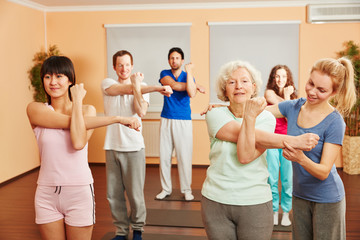 Trainer helps senior woman with yoga exercise