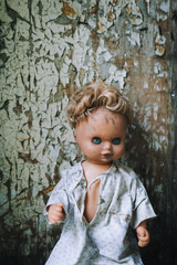 The old doll sits on the background of a wall with cracked paint. fear. horror.